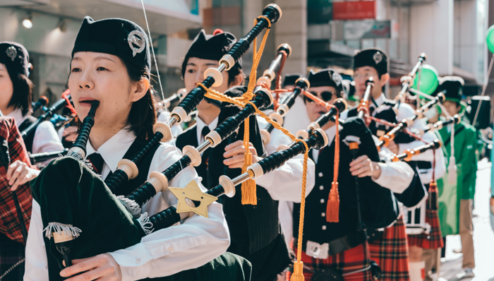 a band marching while playing the bagpipe