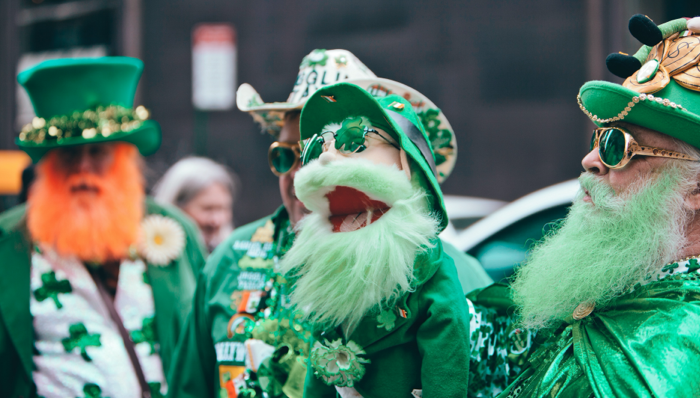 a man holding a puppet of st. patrick's day while celebrating in the streets