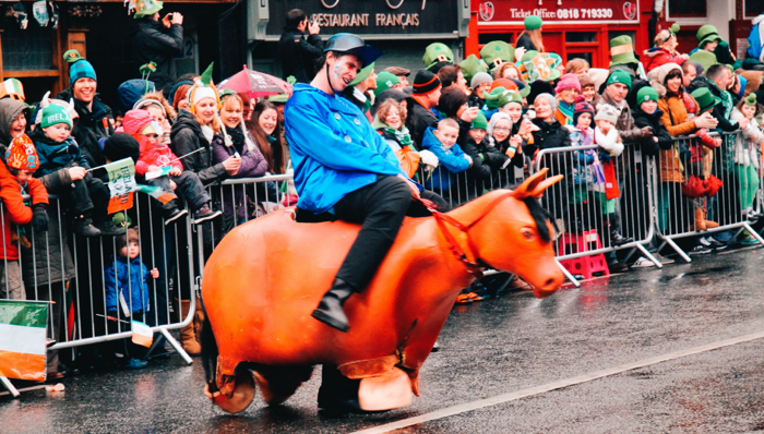 Man dressed in blue wearing a costume of a man riding a horse