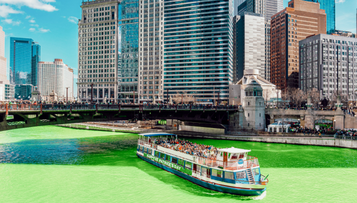 view of a green Chicago river with a river boat passing under a bridge