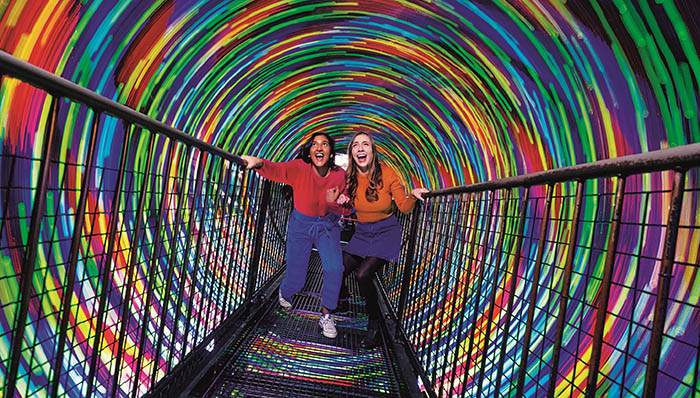 Two women at the Edinburgh Camera Obscura and World of Illusions walking through the swirling light vortex