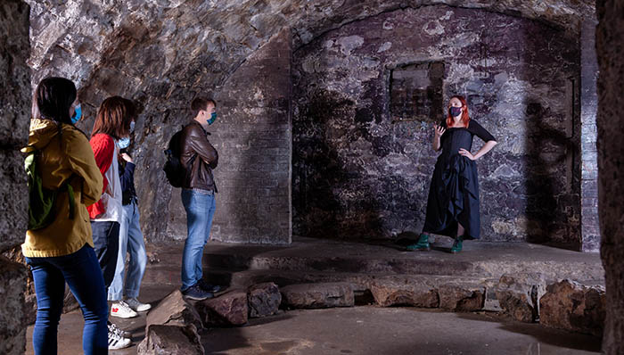 a group enjoying a tour of the underground castle vaults