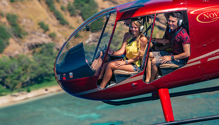 Couple on a helicopter doing a scenic flight on Oahu island, Hawaii, US.