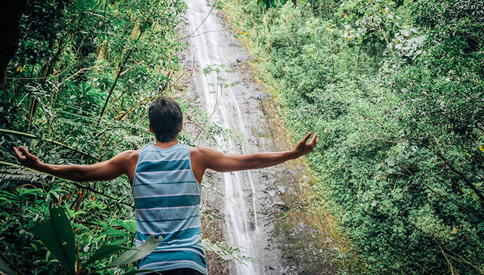 Guy with open arms looking at the Manoa Falls, Oahu, Hawaii after a hike.
