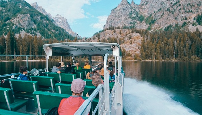 a group of people sitting on a lac cruise boat enjoying the scenic views of the mountain range and nature