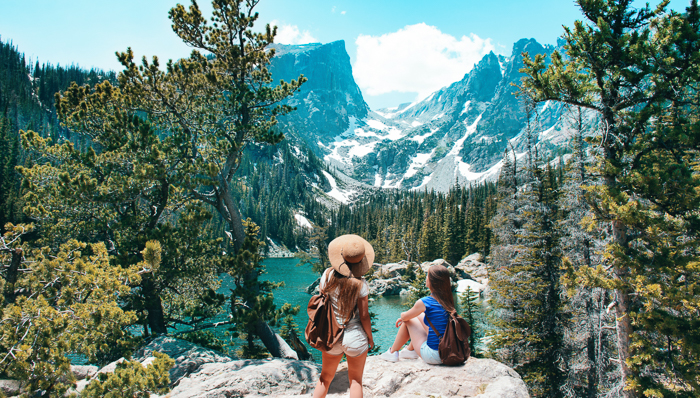 two women hikers taking in the views of the rocky mountains