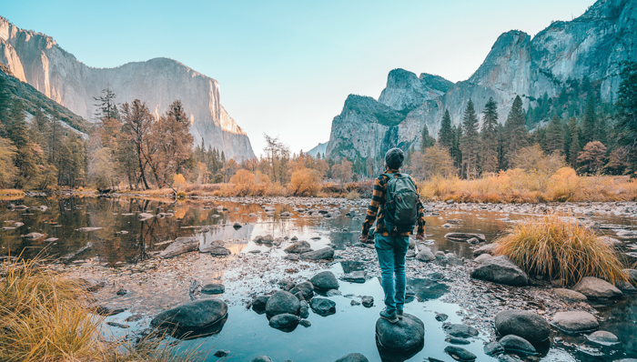 image of a man standing on a rock in a shallow river
