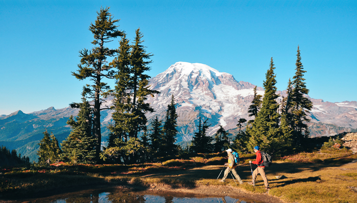 image of a couple of male hikers walking on a trail next to a lake