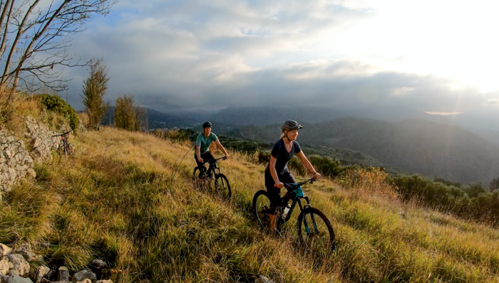 a couple riding bikes on top of a hill