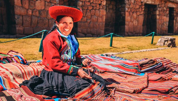 a woman in a traditional peruvian dress making handmade blankets