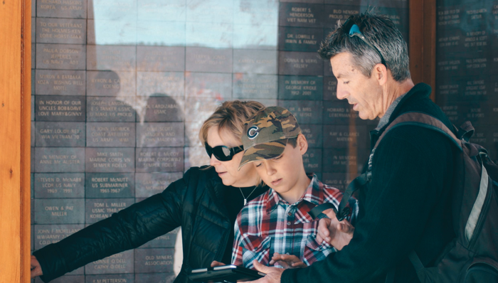 Couple and their son trying to crack the mystery as they look at the clues on a Scavenger Hunt experience.