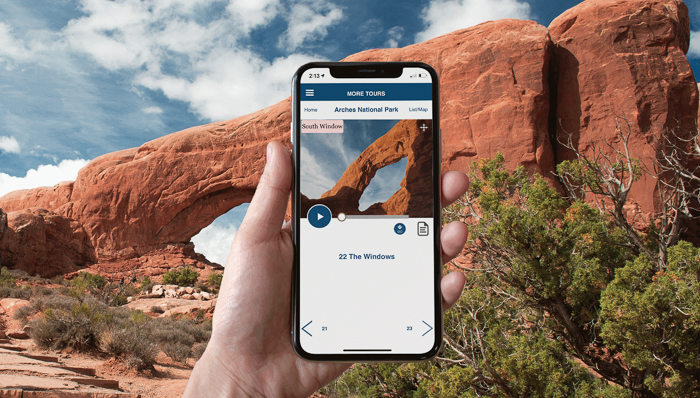 a photo of a hand holding a phone with the self-guided app to arches national park