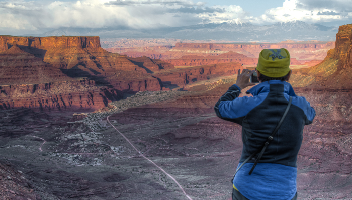 a photo of a man taking a picture of the sunset over arches national park