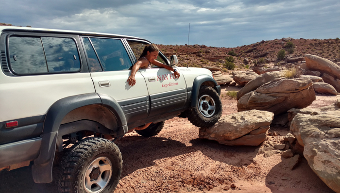 a photo of a 4x4 car climbing over rocks with a woman sitting in the passenger seat