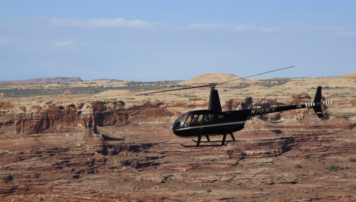 a photo pf a helicopter flying over the rock formations in arches national park
