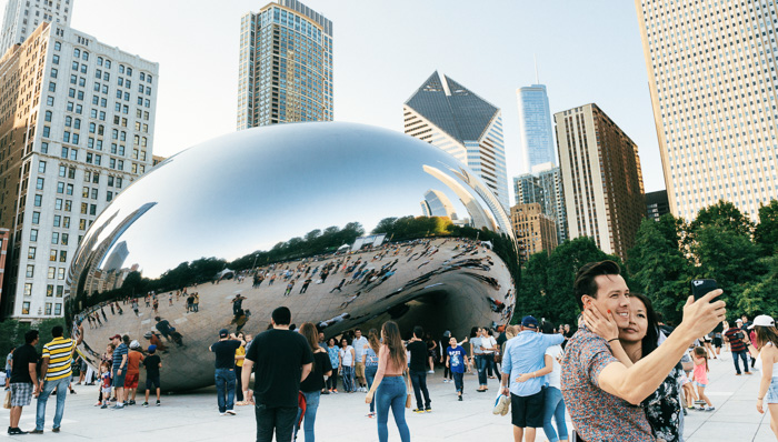 photograph of people crowded around the landmark downtown Chicago's Cloud gate in Millennial Park. The urban cityscape is reflected in the mirrored surface. A couple takes a selfie in the foreground.