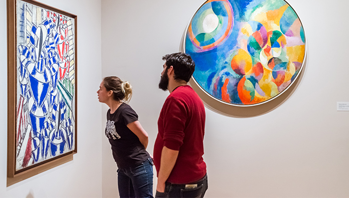 a couple of people admiring a painting