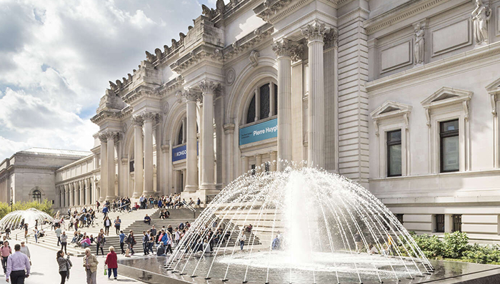 a picture of the infamous steps of the MET and the outside facade of the museum with many groups of people walking and sitting on the steps