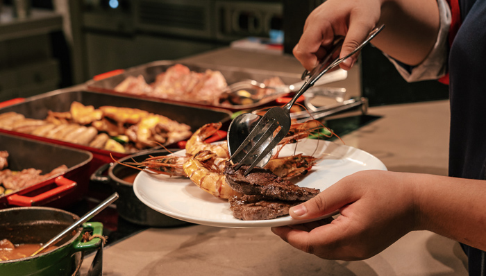 Woman using tongs picking grilled shrimps at buffet restaurant