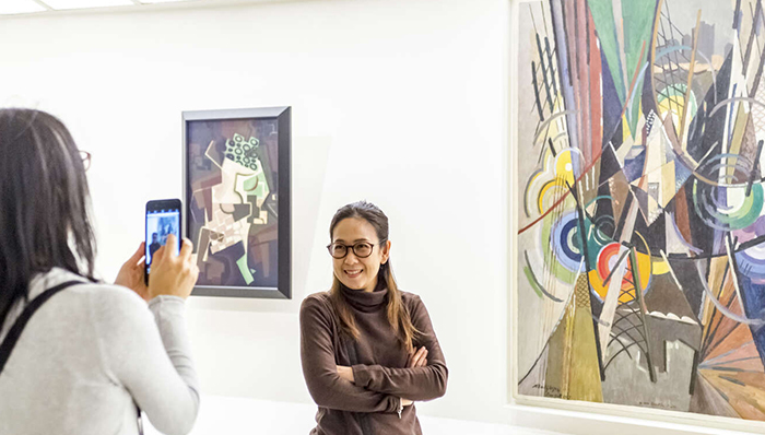 a woman taking a picture of another women who is posing in front of a painting