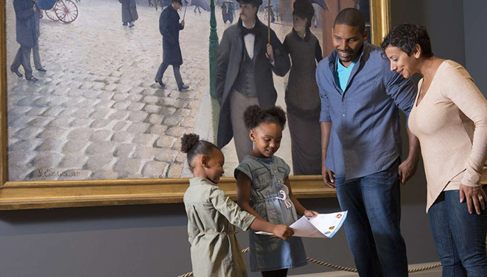 two girls looking at a map of the museum with their parents