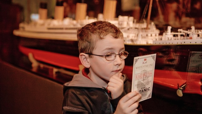 young boy looking at a pamphlet about the titanic while visiting the artifact exhibition in Orlando