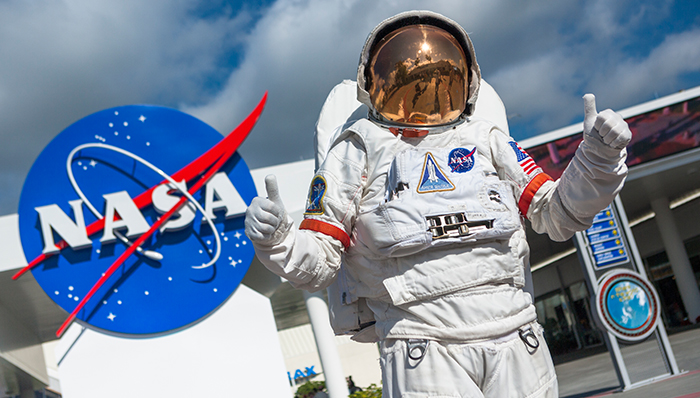 a picture of someone dressed as an astronaut and posing in front of the nasa sign at the Kennedy space center