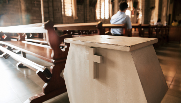 Collection box for generous offertory standing among pews at a Catholic temple