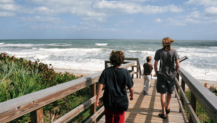 image of a man and two children walking down a boardwalk towards the beach