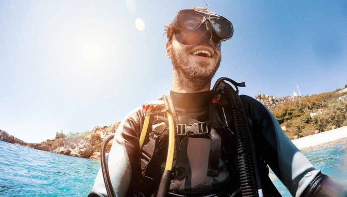 Young diver smiles while prepares for diving.