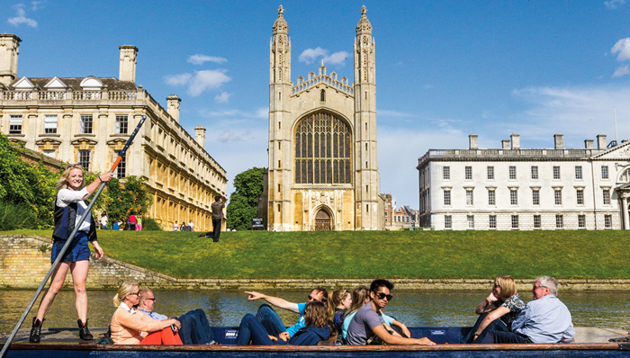 People enjoying a boat ride while crossing the King's College Chapel - Cambridge, UK