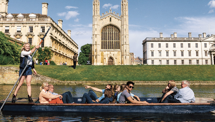 People admiring the view while passing close to the Cambridge University - Cambridge, UK