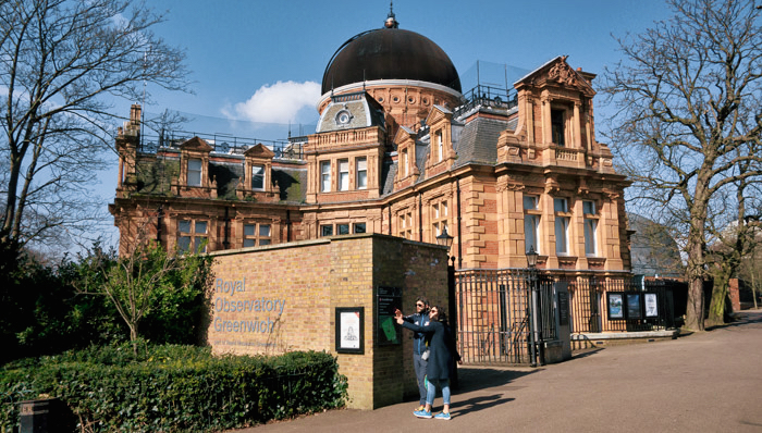 Two tourists outside the south building at The Royal Observatory, Greenwich, London, UK