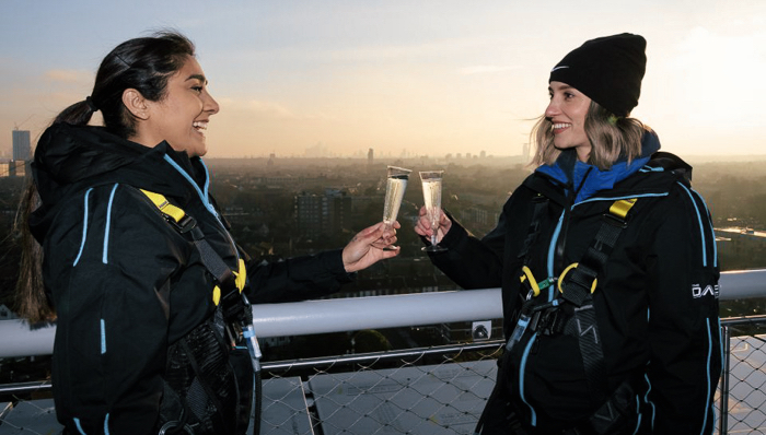 Two girls toasting over the Tottenham Hotspur pitch - London, UK