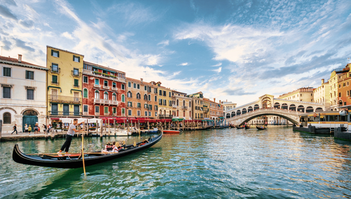 Gondola with tourists on Gran Canal with Rialto Bridge at sunset - Venice, Italy