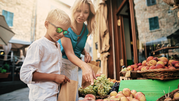 Mother and son buying fresh organic fruits and vegetables in a small Italian town's shop